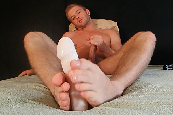 Sexy athletic jock Sean Holmes jerks off while playing a dildo with his feet in Hot Stud Give A FootJob at Gayhoopla